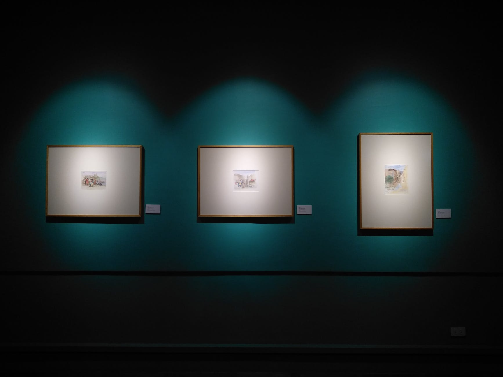 three paintings hanging in gallery